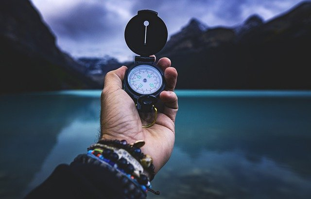 An individual holding a compass.